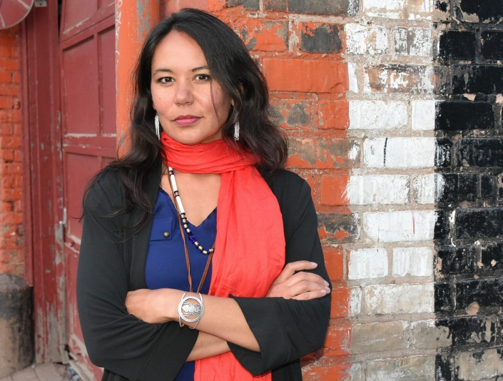 A person, Dr. Michelle Johnson-Jennings, stands against a brick wall, with her arms crossed and looks into the camera.