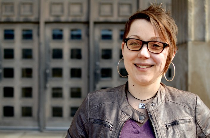 A person, Angela Carter, wears glasses, large hoop earrings, a brown jacket and a purple shirt. She faces the camera and smiles.