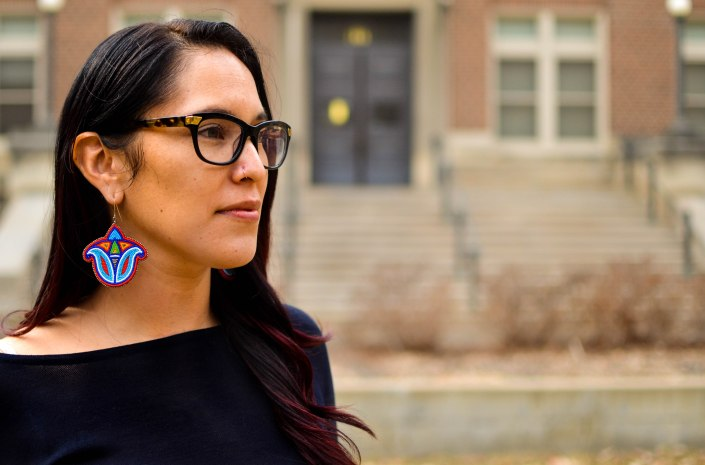 A person, Sasānēhsaeh Pyawasay, has long dark hair and wears glasses, a black shirt, and multicolored earrings. She faces the right, and there is a building in the background.